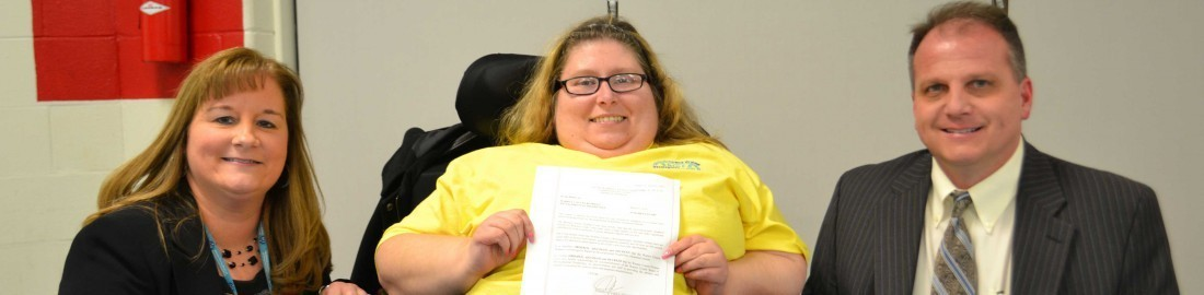 An individual who is served by WCBDD receives a support approval letter from the Superintendent, Megan Manuel,  and a board member.